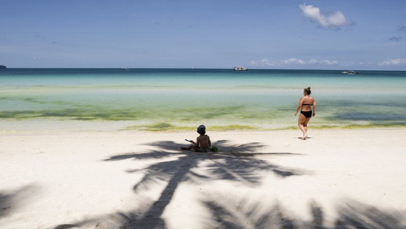 Tourists relax on a beach on the Philippine island of Boracay on April 26, 2018. - The Philippines shuttered its most famous holiday island Boracay to tourists on April 26 for a six-month clean-up, which the government has imposed with a muscular show of its security forces. (Photo by NOEL CELIS / AFP)