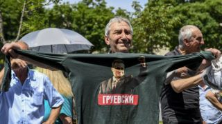A man holds a t-shirt with a picture of former Prime Minister Nikola Gruevski, during a protest in front of the court in Skopje on May 23, 2018. - A Macedonian criminal court has sentenced former conservative prime minister Nikola Gruevski to two years in prison for unlawfully influencing officials at the interior ministry over the purchase of a luxury bulletproof car. (Photo by Robert ATANASOVSKI / AFP)