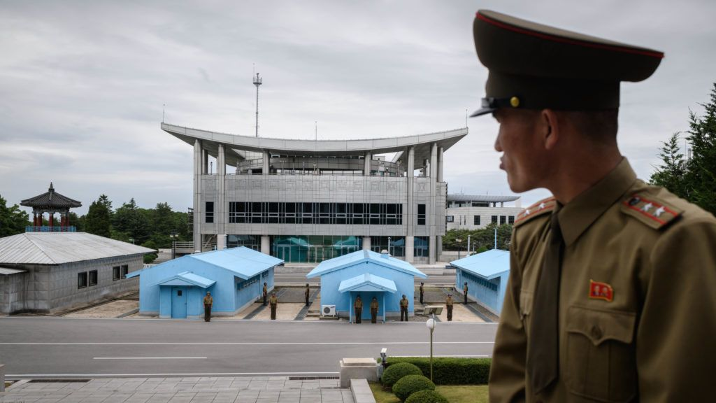 """Korean People's Army soldier Lieutenant Colonel Hwang Myong Jin stands before the South Korean side of the truce village of Panmunjom on the North Korean side of the Demilitarised Zone (DMZ) separating North and South Korea, near Kaesong on June 11, 2018. - On the world's last Cold War frontier, North and South Korean troops have long faced off against each other at Panmunjom, the truce village in the Demilitarised Zone that divides the two Koreas. Now the North Korean troops stationed there express hopes for June 12 unprecedented summit between their commander-in-chief Kim Jong Un and US President Donald Trump. (Photo by Ed JONES / AFP) / """"The erroneous mention[s] appearing in the metadata of this photo by Ed JONES has been modified in AFP systems in the following manner: [Hwang Myong Jin] instead of [Hwang Myong Min]. Please immediately remove the erroneous mention[s] from all your online services and delete it (them) from your servers. If you have been authorized by AFP to distribute it (them) to third parties, please ensure that the same actions are carried out by them. Failure to promptly comply with these instructions will entail liability on your part for any continued or post notification usage. Therefore we thank you very much for all your attention and prompt action. We are sorry for the inconvenience this notification may cause and remain at your disposal for any further information you may require."""""""