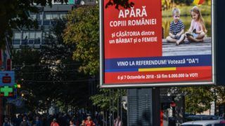 """An outdoor poster reading in Romanian """"Defend the children of Romania and the marriage between a man and a woman, come to the referendum and say """"YES""""""""is pictured downtown Bucharest, Romania on October 2, 2018. Romanians go to the polls on October 6 and 7, 2018 to vote on whether the constitution can characterise marriage as explicitly between a man and woman, an initiative that aims to block same-sex partnerships. From a legal stance nothing will change, no matter the outcome of the vote, for the Romanian law doesn't allow same-sex marriage. But critics of the initiative say an explicit definition of what constitutes a family would make it almost impossible to change the law in favour of same-sex couples. Amnesty International called it a breach of international human rights standards and underlined that it would amount to homophobic discrimination. / AFP PHOTO / Daniel MIHAILESCU"""