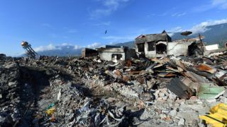 The minaret (back L) of a mosque rests to one side amongst the devastation in the hard-hit area of Balaroa in Palu on October 8, 2018, following the September 28 earthquake and tsunami. Nearly 2000 bodies have been recovered from Palu since an earthquake and tsunami struck the Indonesian city, an official said on October 8, warning the number would rise with thousands still missing. / AFP PHOTO / ADEK BERRY