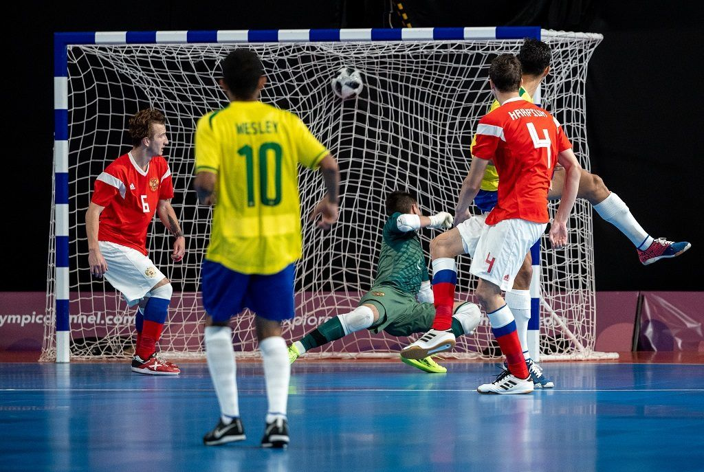 """This handout photo released by the Olympic Information Services (OIS) of the International Olympic Committee (IOC) shows Brazilian Guilherme Henrique Borges Sanches scores during the Gold Medal Match between Brazil and Russia in the Futsal Mens Tournament in the Futsal Main Stadium, Tecnopolis Park during the Youth Olympic Games, in Buenos Aires, Argentina,on October 18, 2018. (Photo by Ivo GONZALEZ / OIS/IOC / AFP) / RESTRICTED TO EDITORIAL USE - MANDATORY CREDIT """"AFP PHOTO / OIS/IOC - IVO GONZALEZ"""" - NO MARKETING - NO ADVERTISING CAMPAIGNS - DISTRIBUTED AS A SERVICE TO CLIENTS"""