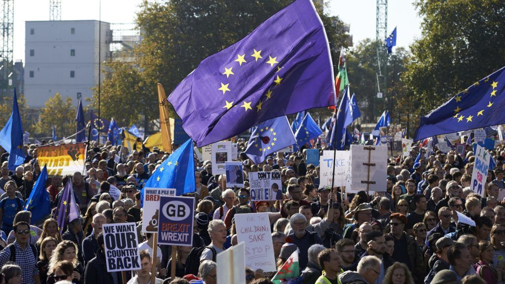 Demonstrators hold placards and European Union flags as they take part in a march calling for a People's Vote on the final Brexit deal, in central London on October 20, 2018. - Britons dreading life outside Europe gathered from all corners of the UK to London on Saturday to try to stop their country's looming breakup with the EU. (Photo by NIKLAS HALLE'N / AFP)