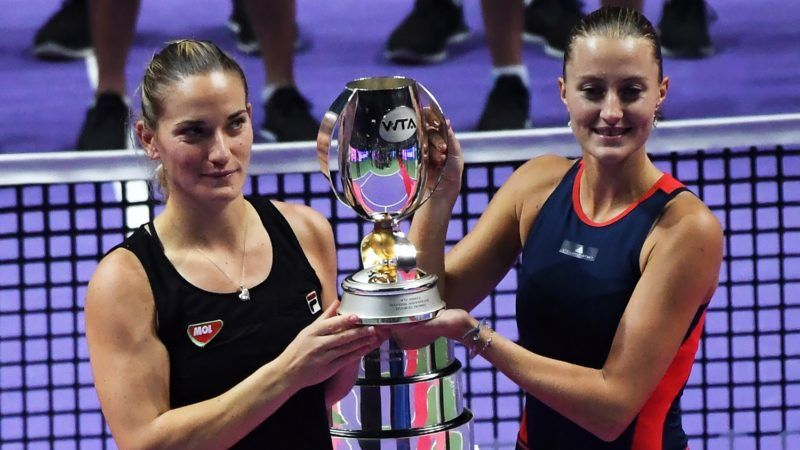 Timea Babos of Hungary (L) and her teammate Kristina Mladenovic of France hold up their winning trophy after defeating Czech Republic's Barbora Krejcikova and Katerina Siniakova during the women doubles final match at the WTA Finals tennis tournament in Singapore on October 28, 2018. (Photo by Roslan RAHMAN / AFP)