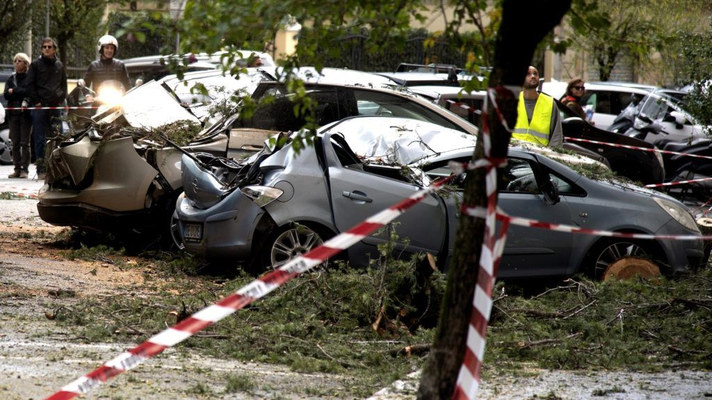 The picture taken on October 30, 2018 show cars damaged during bad weather in the Prati district of Rome. (Photo by Tiziana FABI / AFP)