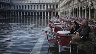 """Two people sit on a terrace in St. Mark's Square during an ''acqua-alta'' or high-water in Venice on November 12, 2016. - The rise in the water level is due to winds and currents and can flood some parts of the city in a yearly phenomenon known as """"acqua alta"""" (high water). (Photo by MARCO BERTORELLO / AFP)"""