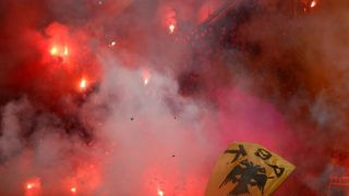 ATHENS, GREECE - NOVEMBER 11:  AEK fans burn flares during the Superleague match between AEK Athens and Olympiacos Piraeus at OAKA Stadium on November 11, 2012 in Athens, Greece.  (Photo by Vladimir Rys Photography/Getty Images)