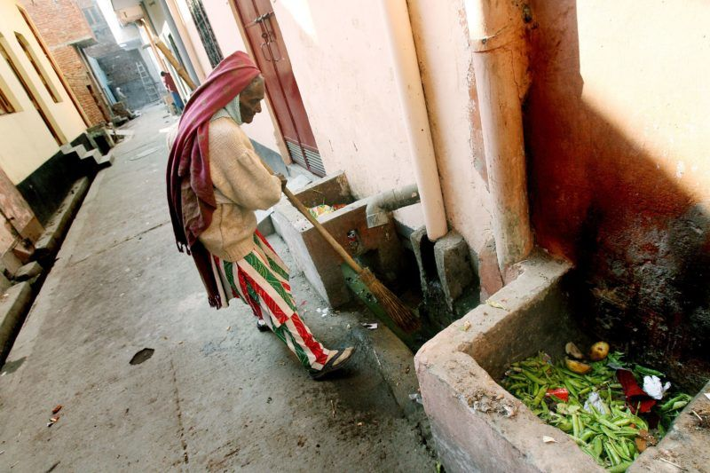 """In this photo taken, 15 January 2007, Chandrawati, sweeper and drain cleaner by profession, cleans out a drain in the Shahdara area of eastern New Delhi.  In 1993, the government banned the practice, known as """"manual scavenging"""" which existed for centuries before flush toilets were introduced. Under the law, the construction of dry toilets is banned and existing ones are supposed to be demolished. The law also provides for retraining of people doing the job, 04 February 2007. The national government set 2007 as a deadline to eradicate the practice, but officials admitted privately it would take at least three more years to find new employment for the workers.  AFP PHOTO/Prakash SINGH (Photo by PRAKASH SINGH / AFP)"""