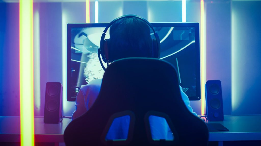 Back View Shot of the Professional Gamer Playing in First-Person Shooter Online Video Game on His Personal Computer. Room Lit by Neon Lights in Retro Arcade Style. Online Cyber e-Sport Internet Championship.