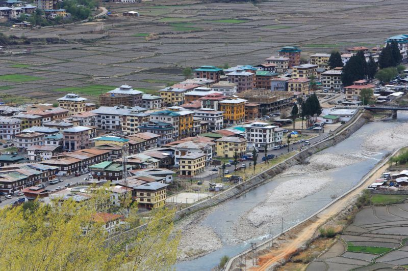 """View of Paro city and valley Valley in Bhutan. Paro (Dzongkha) is an ancient town in the homonymous valley, with many sacred sites, temples and historical buildings. It is also home to Paro Airport, Bhutan's sole international airport. The Kingdom of Bhutan is landlocked in the Eastern Himalayas, Thimphu is its capital and largest city, while Phuntsholing is its financial center. The Head of state is the King of Bhutan, known as the """"Dragon King"""". Never colonized, the Kingdom sits on the ancient Silk Road between Tibet, Indian and Southeast Asia. Bhutan is famous for pioneering the concept of Gross National Happiness."""