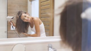 Happy woman drying her hair in bathroom. Photo taken through glass