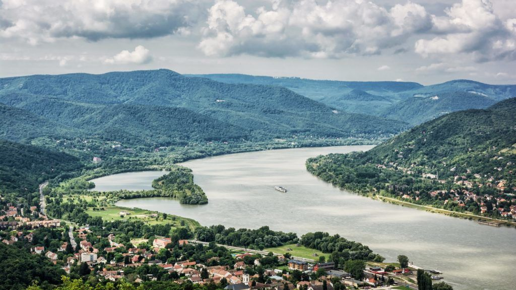 View from Ruin castle of Visegrad, Hungary. Danube river. Travel destination. Sightseeing cruises. Forests, clouds and flowing water.