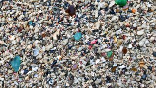 Image of the broken glass with sand on the beach.