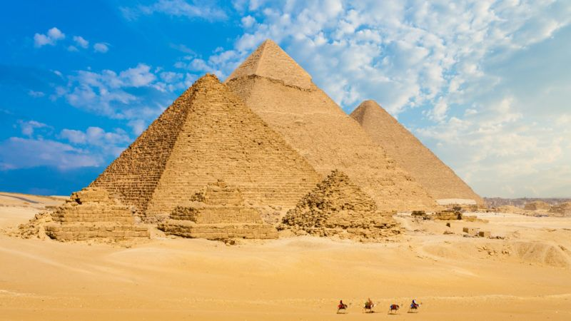 All Egyptian Pyramids from distance with row of camels walking in foreground in Giza, Cairo, Egypt.  Wide telephoto shot plenty of copy space.