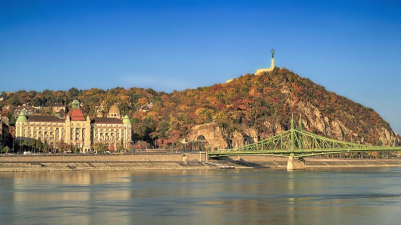 The Gellert Hill (Hungarian: Gellért hegy) and the Danube river (Hungarian: Duna)  in Budapest at autumn. At the foot of the mountain can be found the Hotel Gellert and the Gellert Thermal Bath. On the right side is the Freedom / Liberty Bridge (Hungarian: Szabadság híd).