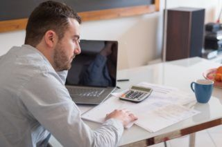 Frustrated man calculating bills and tax  expense