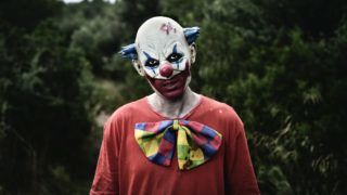closeup of a scary evil clown wearing a dirty red costume in the woods