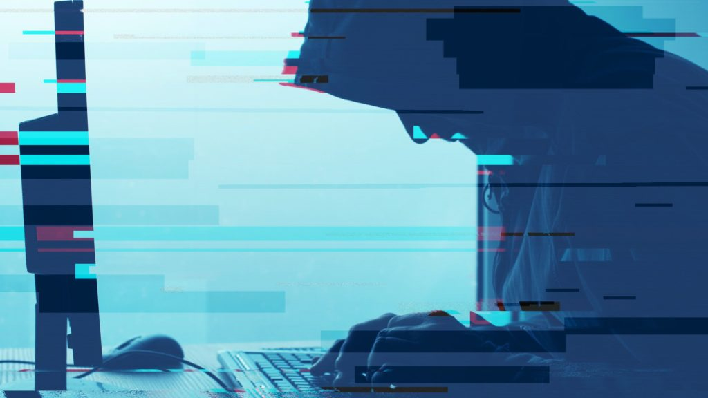 Hooded computer hacker working on desktop PC computer. P2P and piracy, computer virus and trojans, phishing, malware and ransomware concept with glitch effect.
