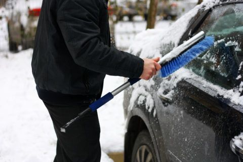 Snowy winter. The snow machine. A man cleans snow from the car with the help of special brushes.