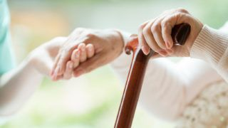 Elder person supported on wooden stick during rehabilitation in friendly hospital
