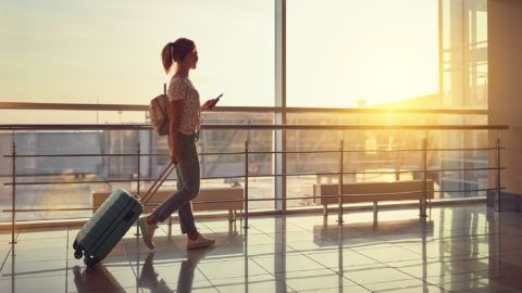young woman goes  at airport  at window  with a suitcase waiting for  plane