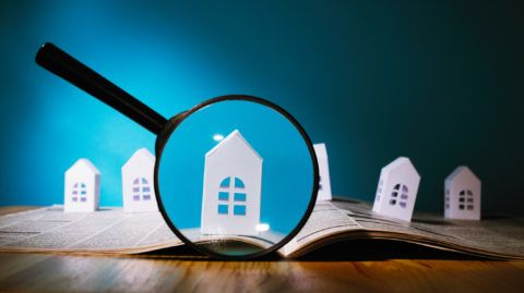 Magnifying glass in front of an open newspaper with paper houses. Concept of rent, search, purchase real estate.