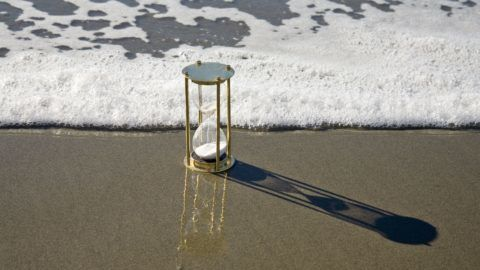 Hourglass on beach in front of approaching wave, just before being overwhelmed. More sand timer:-[url=//www.istockphoto.com/file_search.php?action=file&lightboxID=3832397]here[/url].
