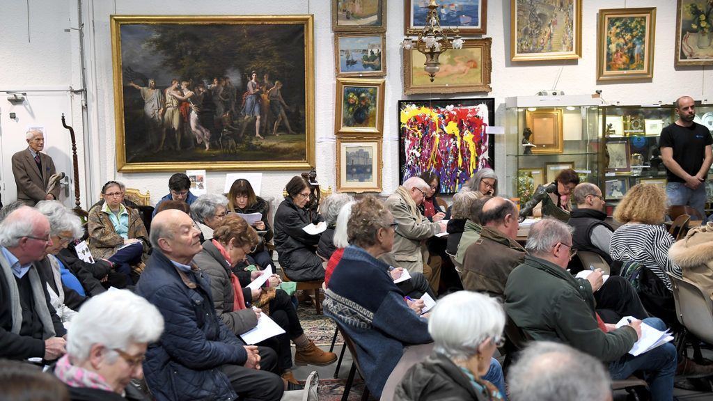 People take part in an auction sale in front of a painting by French Charles Meynier (L) (1768-1832) acting 'Telemachus, urged by Mentor, leaving the island of Calypso' on March 27, 2018 in Nantes, western France. - The painting was sold at 2.232 millions of euros, 10 times more its estimate price (between 150.000 and 250.000 euros). (Photo by LOIC VENANCE / AFP)