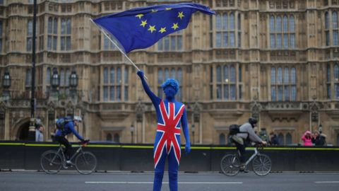 A anti-Brexit demonstrator dressed in a Union Flag suit and waving an EU flag stands on the road outside the Houses of Parliament in central London on March 29, 2018. - The one-year countdown to Britain's exit from the European Union began on March 29, 2018 with Prime Minister Theresa May touring the UK shore up support for the government's Brexit strategy. (Photo by Daniel LEAL-OLIVAS / AFP)