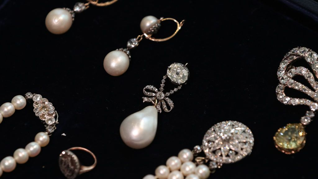 """The 'Queen Marie Antoinette's Pearl' (C) with an estimated value of Ł767,500-Ł1,534,000 GBP (872,500-1,743,000 Euros, $1,000,000-2,000,000 USD) is pictured with other jewellery during a photocall for the sale of 'Royal Jewels from the Bourbon Parma Family' at Sotheby's auction house in London on October 19, 2018. - One of the most important royal jewellery collections ever to come to auction comes for sale at Sotheby's in Geneva on November 14, 2018. Entitled """"Royal Jewels from the Bourbon-Parma Family"""", the auction will span centuries of European history, from the reign of Louis XVI to the fall of the Austro-Hungarian Empire, (Photo by Daniel LEAL-OLIVAS / AFP)"""