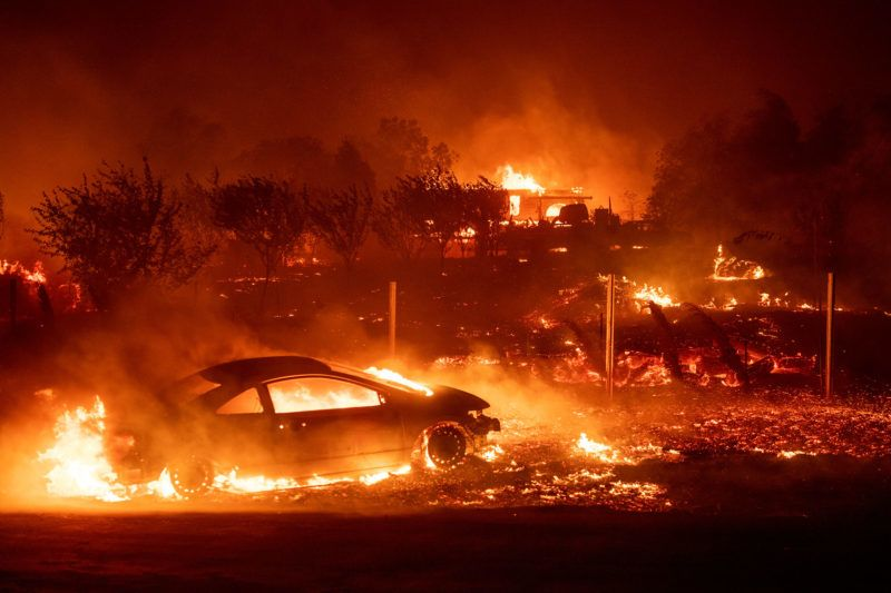 Vehicles and homes burn as the Camp fire tears through Paradise, California on November 8, 2018. - More than 18,000 acres have been scorched in a matter of hours burning with it a hospital, a gas station and dozens of homes. (Photo by Josh Edelson / AFP)