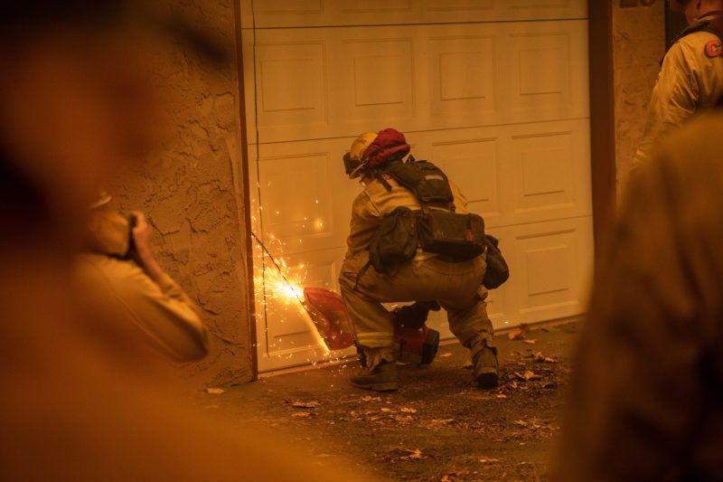 A fireman cuts into a garage door at a burning Shadowbrook apartment complex in Paradise, north of Sacramento, California on November 09, 2018. - A rapidly spreading, late-season wildfire in northern California has burned 20,000 acres of land and prompted authorities to issue evacuation orders for thousands of people. As many as 1000 homes, a hospital, a Safeway store and scores of other structures have burned in the area as the Camp fire tore through the region. (Photo by Josh Edelson / AFP)