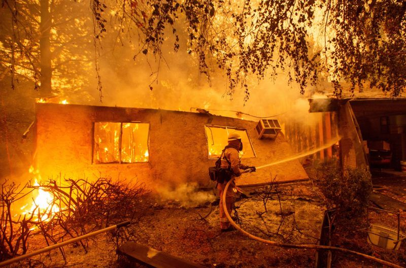 Firefighters battle flames at a burning apartment complex in Paradise, north of Sacramento, California on November 09, 2018. - A rapidly spreading, late-season wildfire in northern California has burned 20,000 acres of land and prompted authorities to issue evacuation orders for thousands of people. As many as 1000 homes, a hospital, a Safeway store and scores of other structures have burned in the area as the Camp fire tore through the region. (Photo by Josh Edelson / AFP)