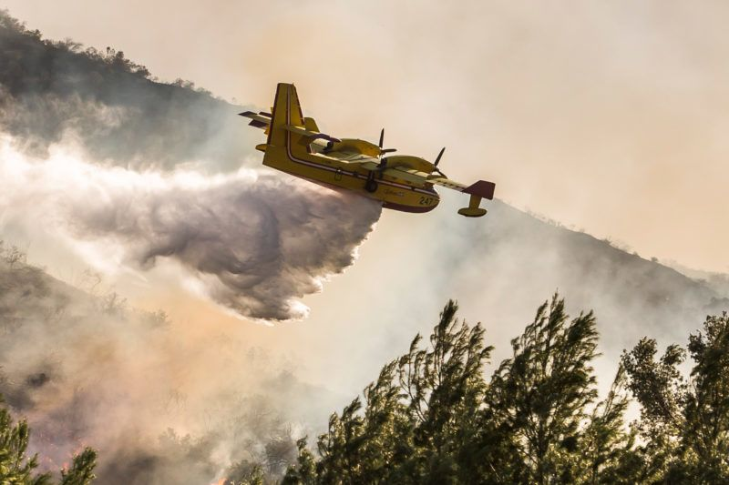 An airplane drops water on wildfires close to the 101 Freeway in Thousands Oaks, California on November 09, 2018. - California officials say people have died in the wildfires but havent said how many. More than 150,000 people have evacuated. (Photo by Apu Gomes / AFP)