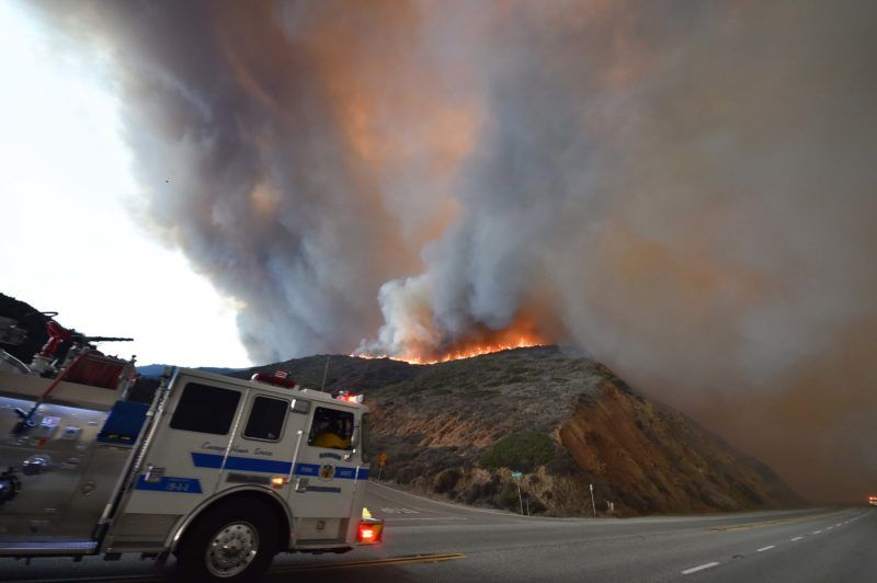 A fire truck drives south on the Pacific Coast Highway (Highway 1) as the Woolsey Fire advances toward the ocean in Malibu, California, November 9, 2018. - About 75,000 homes have been evacuated in Los Angeles and Ventura counties due to two fires in the region. (Photo by Robyn Beck / AFP)