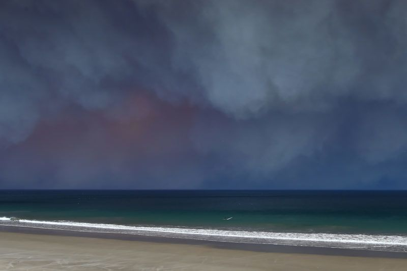 A man sits on his surfboard in the Pacific Ocean under the smoke from the Woolsey Fire on November 9, 2018 in Malibu, California, November 9, 2018. - About 75,000 homes have been evacuated in Los Angeles and Ventura counties due to two fires in the region. (Photo by Robyn Beck / AFP)