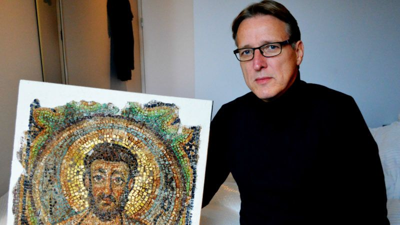 Dutch art detective Arthur Brand poses with the missing mosaic of St Mark, a rare piece of stolen Byzantine art from Cyprus, in a hotel room in The Hague on November 17, 2018. - Brand said he handed back the artwork to Cypriot authorities on the same day. (Photo by Jan HENNOP / AFP)