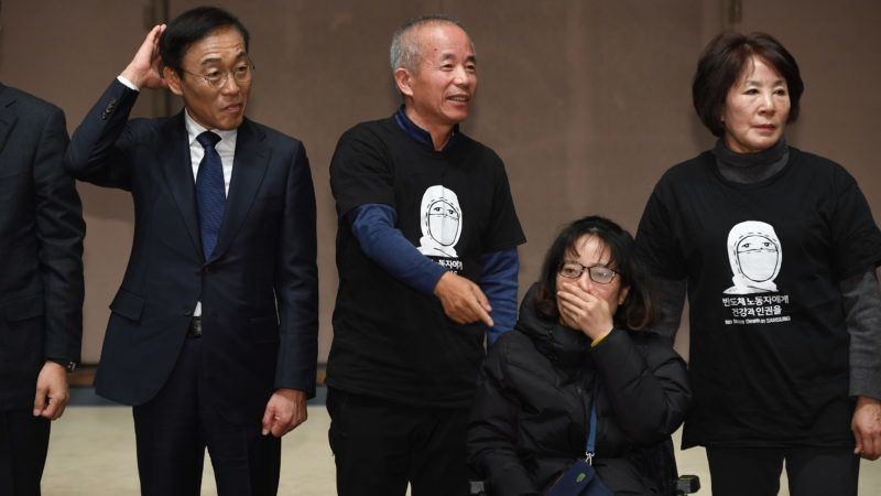 Samsung Electronics co-president Kim Ki-nam (L) poses for a photo with relatives of victims of work-related diseases of its semiconductor and LCD factories after he made a formal apology in Seoul on November 23, 2018. - Samsung Electronics apologised on November 23 to workers who developed cancer after working at its semiconductor factories, finally ending a decade-long dispute at the world's top chipmaker. (Photo by Jung Yeon-je / AFP)
