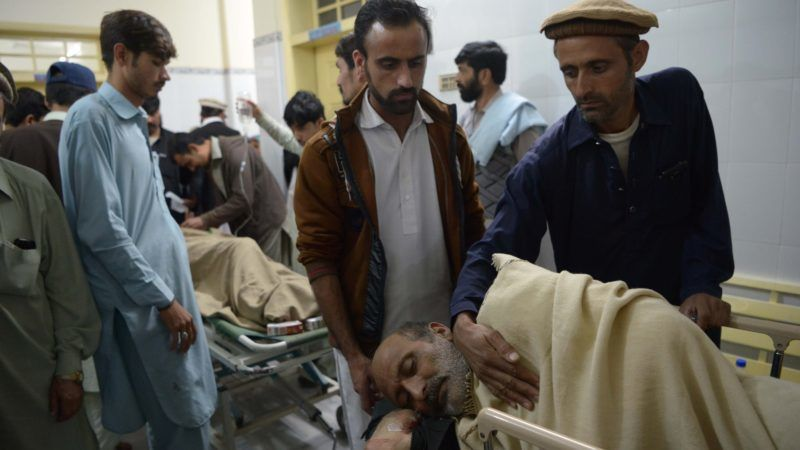 Relatives look over an injured bomb blast victim after at a hospital in Kohat on November 23, 2018, following a marketplace bombing. - At least 31 people were killed and 50 wounded when a bomb hidden in a carton of vegetables ripped through a crowded marketplace in Pakistan's restive northwestern tribal region November 23, officials said. (Photo by ABDUL MAJEED / AFP)