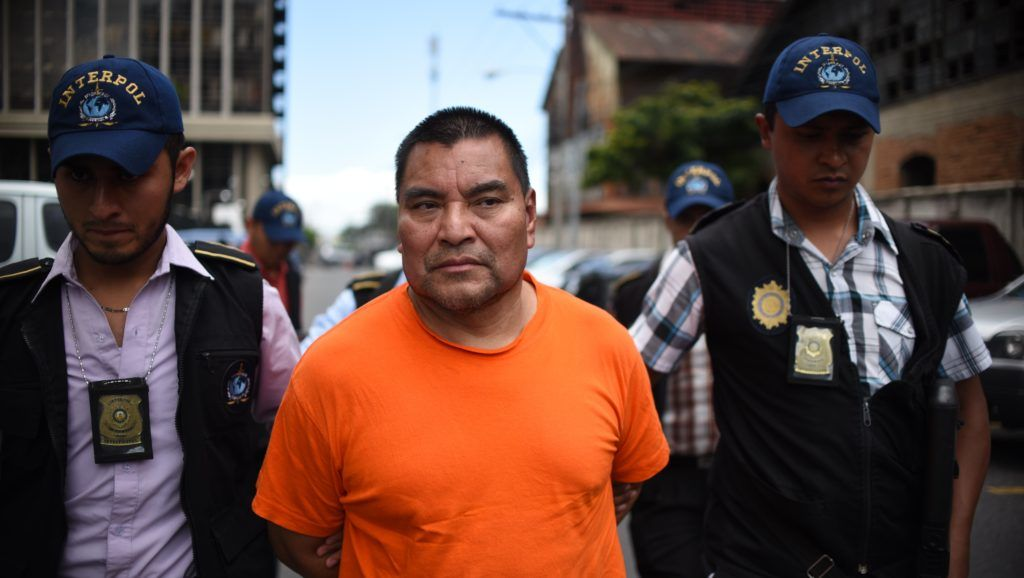 Former Guatemalan soldier Santos Lopez Alonzo is escorted by Interpol agents upon landing at the Air Force base in Guatemala City, on August 10, 2016, after being deported from the US. - Lopez is accused of participating in the massacre of 201 peasants in 1982 in the north of the country. (Photo by JOHAN ORDONEZ / AFP)