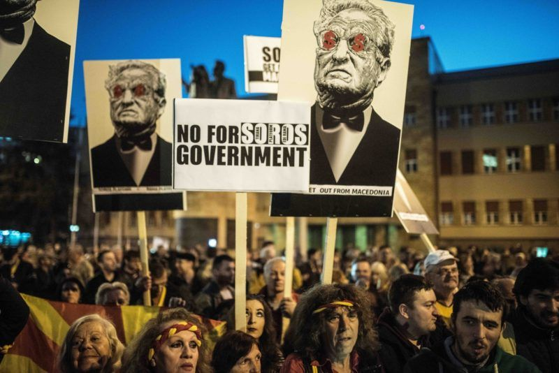 People hold anti-Soros banners during a demonstration against a deal between Social Democrats and the Albanian Democratic Union for Integration, for a law making Albanian the second official language, on March 20, 2017 in Skopje. - The European Union's enlargement commissioner, Johannes Hahn, will visit Macedonia on March 21 in another bid to help break a political deadlock that has left the country's parties unable to form a government since an election in December. (Photo by Robert ATANASOVSKI / AFP)
