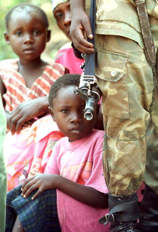 A member of the rebel forces in the Democratic Republic of Congo opposing government forces of president Laurent Desire Kabila hold his war gun 22 August in Goma as kids look at the photographer. Rebel forces announced 22 August they downed two Zimbabwean fighter planes providing military support to DRC president Kabila. (Photo by ABDELHAK SENNA / AFP)