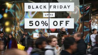Shoppers pass a promotional sign for 'Black Friday' sales discounts on Oxford Street in London, on November 24, 2017. - Black Friday is a sales offer originating from the US where retailers slash prices on the day after the Thanksgiving holiday. In the UK it is used as a marketing device to entice Christmas shoppers with the discounts at stores often lasting for a week. (Photo by Daniel LEAL-OLIVAS / AFP)