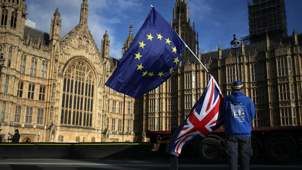 A pro-European Union,(EU), anti-Brexit demonstrator holds the EU and UK flags outside the Houses of Parliament, in central London on January 22, 2018. (Photo by Daniel LEAL-OLIVAS / AFP)