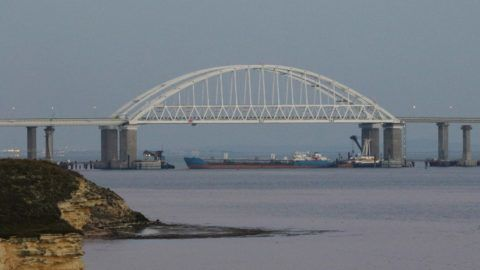 5711848 25.11.2018 A cargo ship blocks a passage under the arch of the Crimean bridge over Kerch Strait in Russia, November 25, 2018. On Sunday Russian authorities closed off the Kerch Strait after three Ukrainian naval ships had crossed the Russian border and entered the temporarily closed area of the Russian territorial waters.  Andrej Krylov / Sputnik