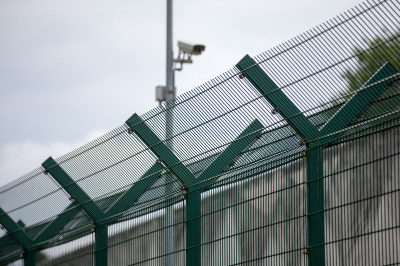 09 July 2018, Germany, Bueren: View onto a gate and a security camera of the accommodation facility for persons facing deportation by the Detmold district government. The facility serves the purpose of custody and care of foreigners and safeguarding deportation. Photo: Friso Gentsch/dpa