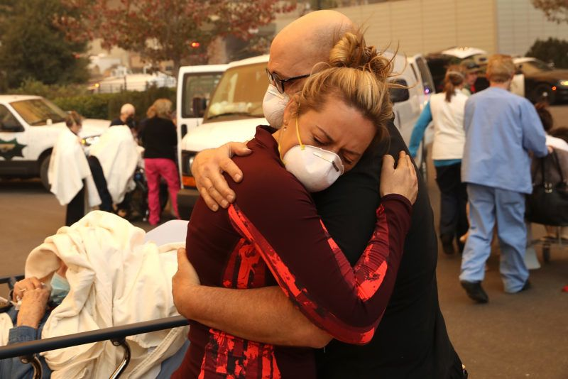 PARADISE, CA - NOVEMBER 08: A hospital worker embraces her co-worker as they evacuate patients from the Feather River Hospital during the Camp Fire on November 8, 2018 in Paradise, California. Fueled by high winds and low humidity, the rapidly spreading Camp Fire has ripped through the town of Paradise and has quickly charred 18,000 acres and has destroyed dozens of homes in a matter of hours. The fire is currently at zero containment.   Justin Sullivan/Getty Images/AFP