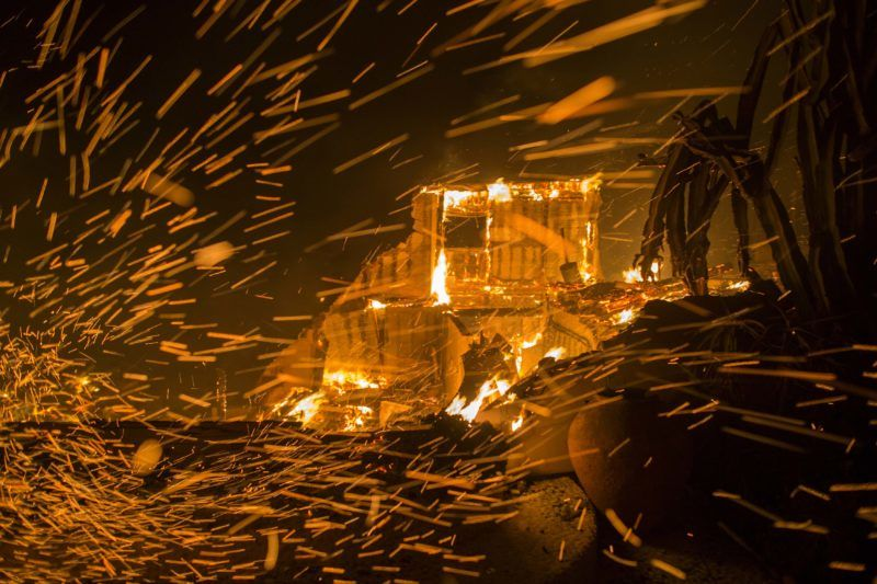 MALIBU, CA - NOVEMBER 09: Strong winds blow embers from burning houses during the Woolsey Fire on November 9, 2018 in Malibu, California. After a experiencing a mass shooting, residents of Thousand Oaks are threatened by the ignition of two nearby dangerous wildfires, including the Woolsey Fire which has reached the Pacific Coast at Malibu.   David McNew/Getty Images/AFP