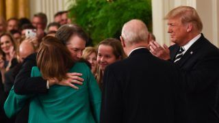 US president Donald Trump applauds as newly sworn-in Associate Justice of the US Supreme Court Brett Kavanaugh hugs his wife Ashley Estes, October 8, 2018 at the White House in Washington, DC. (Photo by Brendan Smialowski / AFP)