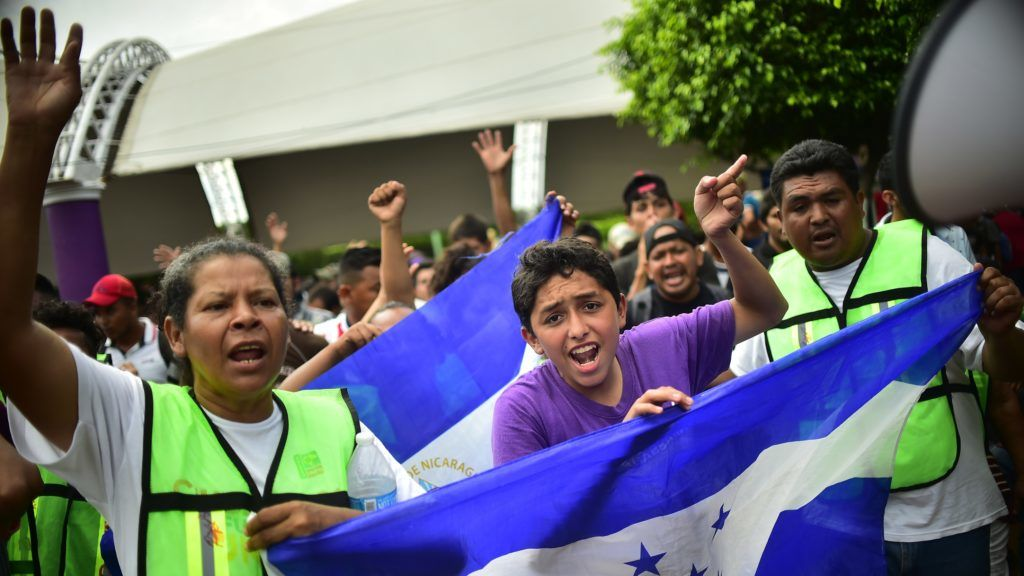 Honduran migrants heading in a caravan to the US, who have already reached Mexican soil, cheer at the rest of the group still waiting to cross at the Guatemala-Mexico border bridge, in Ciudad Hidalgo, Chiapas state, Mexico after crossing from Guatemala, on October 20, 2018. - Thousands of migrants who forced their way through Guatemala's northwestern border and flooded onto a bridge leading to Mexico, where riot police battled them back, on Saturday waited at the border in the hope of continuing their journey to the United States. (Photo by Pedro Pardo / AFP)